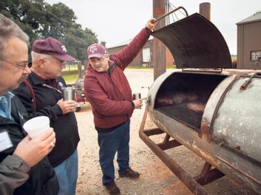 As Texas A&M professor Davey Griffin demonstrates, frequent monitoring of the smoker is part of the job. But don't open the lid too much; that's a no no.