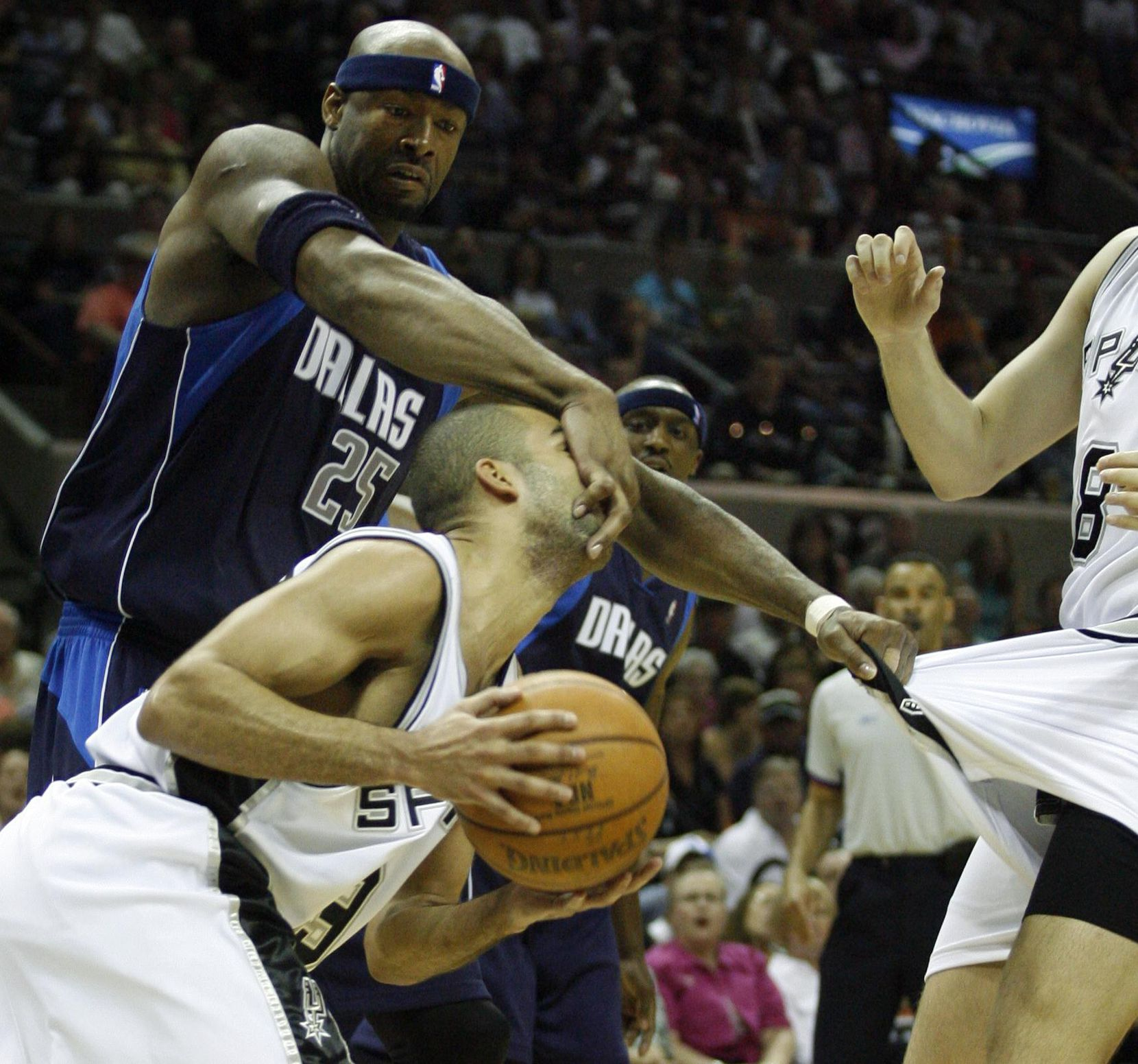 Dallas Mavericks Erick Dampier (25) grabs the face of San Antonio Spurs Tony Parker (9) and the shorts of Rasho Nesterovic (8) during the second half of game 1 of the Western Conference Playoffs Semifinals Playoffs game 1 in San Antonio on Sunday, May 7, 2006. The Spurs defeated the Mavericks 87-85.