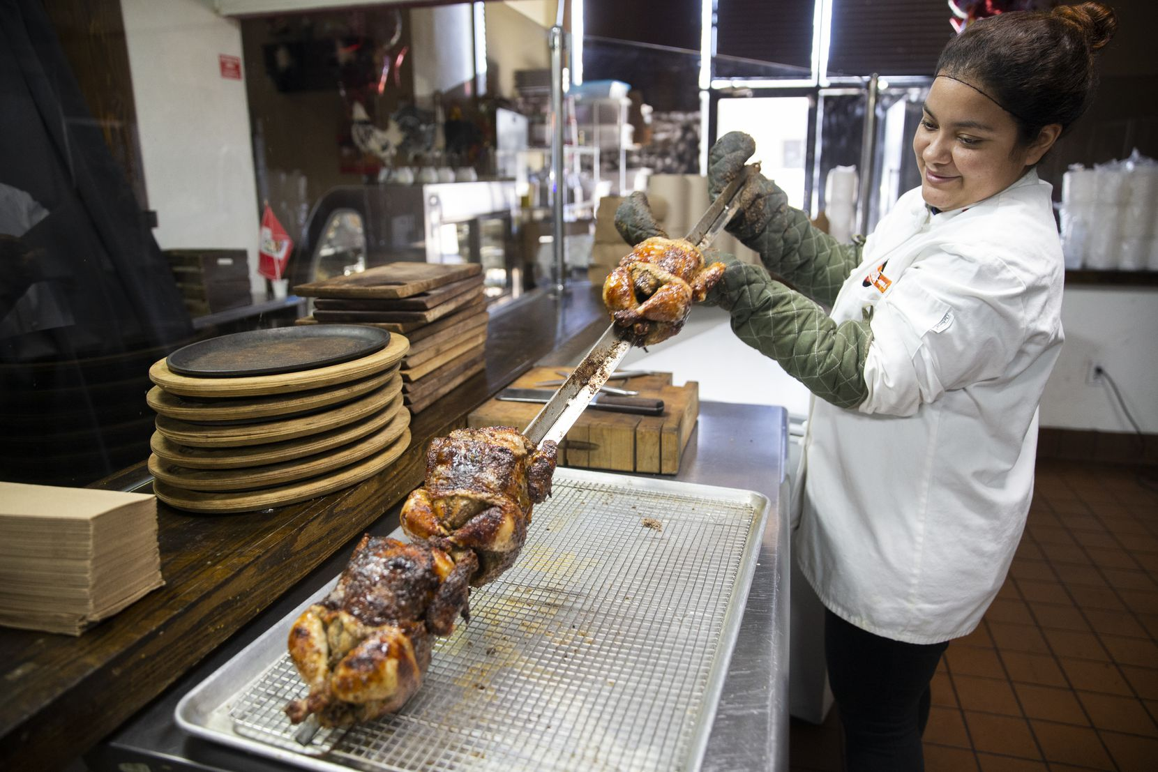 Jenny Lopez takes the pollo a la brasa (Peruvian roasted chicken) out of the oven at the Brasa Bar and Grill in Richardson.