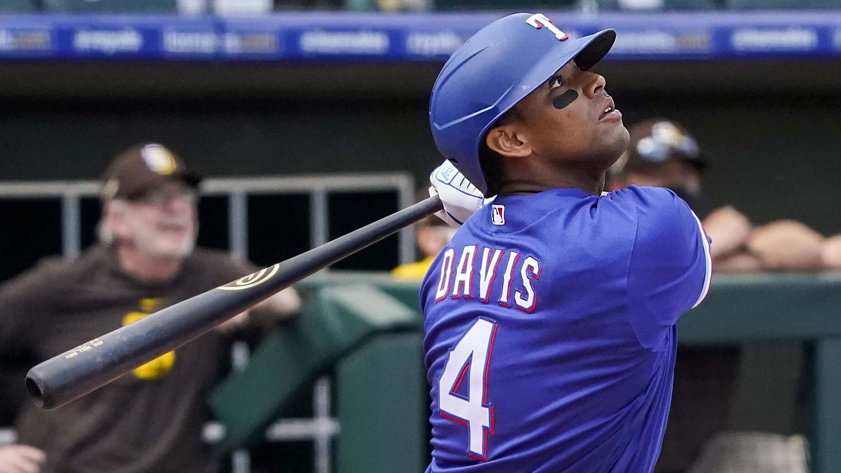 Texas Rangers designated hitter Khris Davis watches the ball as he flies out to right field during the first inning of a spring training game against the San Diego Padres at Surprise Stadium on Thursday, March 4, 2021, in Surprise, Ariz.
