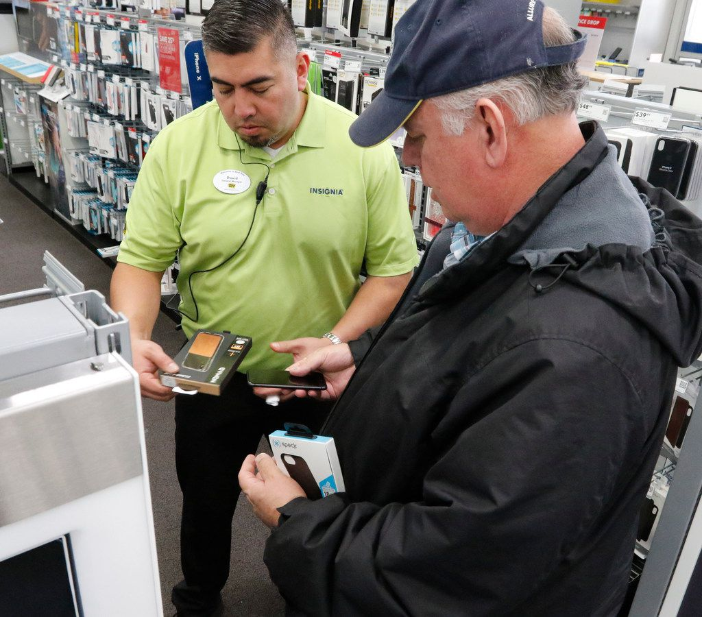 Best Buy General Manager David Gonzales, left, helps Gerald Lindsey, right, find an iPhone case as customers did last-minute Christmas Eve shopping at Best Buy on North Central Expy in Dallas on December 24, 2017.