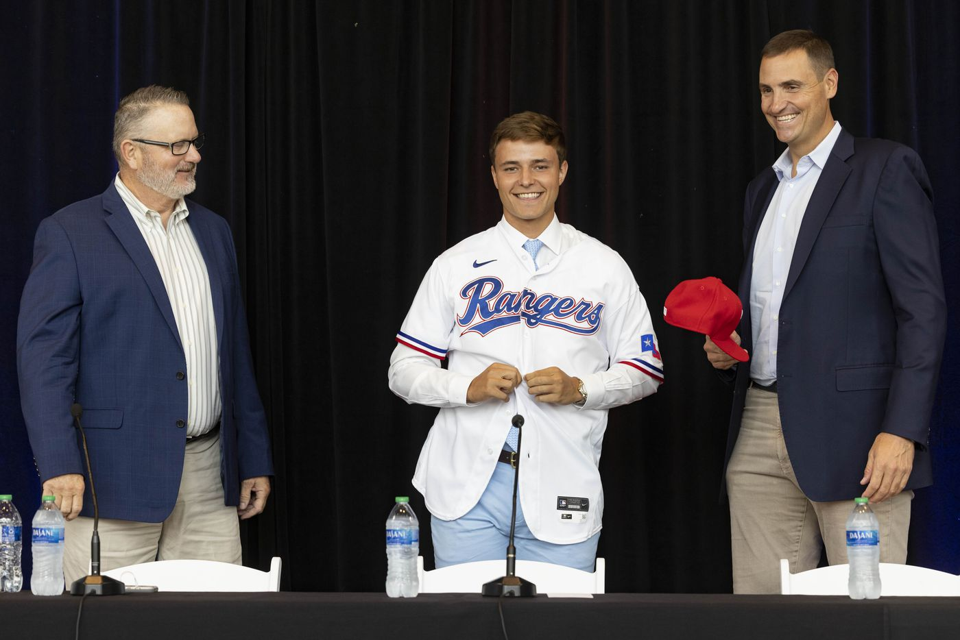Kip Fagg (left), Texas Rangers Senior Director of Amateur Scouting, and Chris Young (right), Rangers Executive Vice President and General Manager, watch as right-handed pitcher Jack Leiter from Vanderbilt University puts on his Texas Rangers jersey following the announcement of his signing on Tuesday, July 27, 2021, at Globe Life Field in Arlington. Leiter was the club's 2021 MLB Draft first round selection and the draft's second overall pick. (Juan Figueroa/The Dallas Morning News)