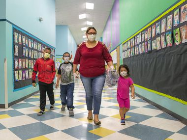 Angie Andrade (center) and her children (from left) Angel, 10, Austin, 7, and Abigail, 3, wear face masks as they walk to pick up free sack lunches at J.T. Saldivar Elementary School in Dallas Tuesday, March 17, 2020. DISD typically provides breakfast and lunch during spring break for any student wishing to drop by for a meal, but in light of the COVID-19 pandemic, some families have practiced extra caution in picking up meals. (Lynda M. Gonzalez/The Dallas Morning News)