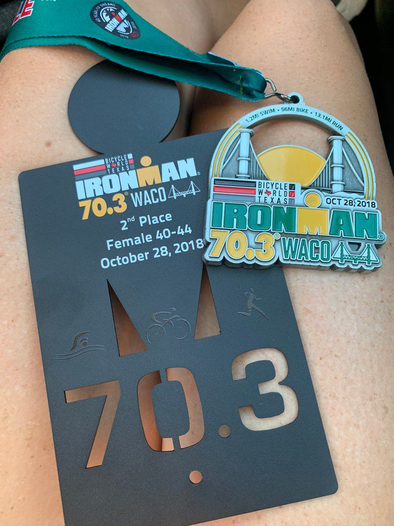 The finishers  medal and Brandi Grissom Swicegood's 2nd place trophy from Ironman 70.3 Waco.