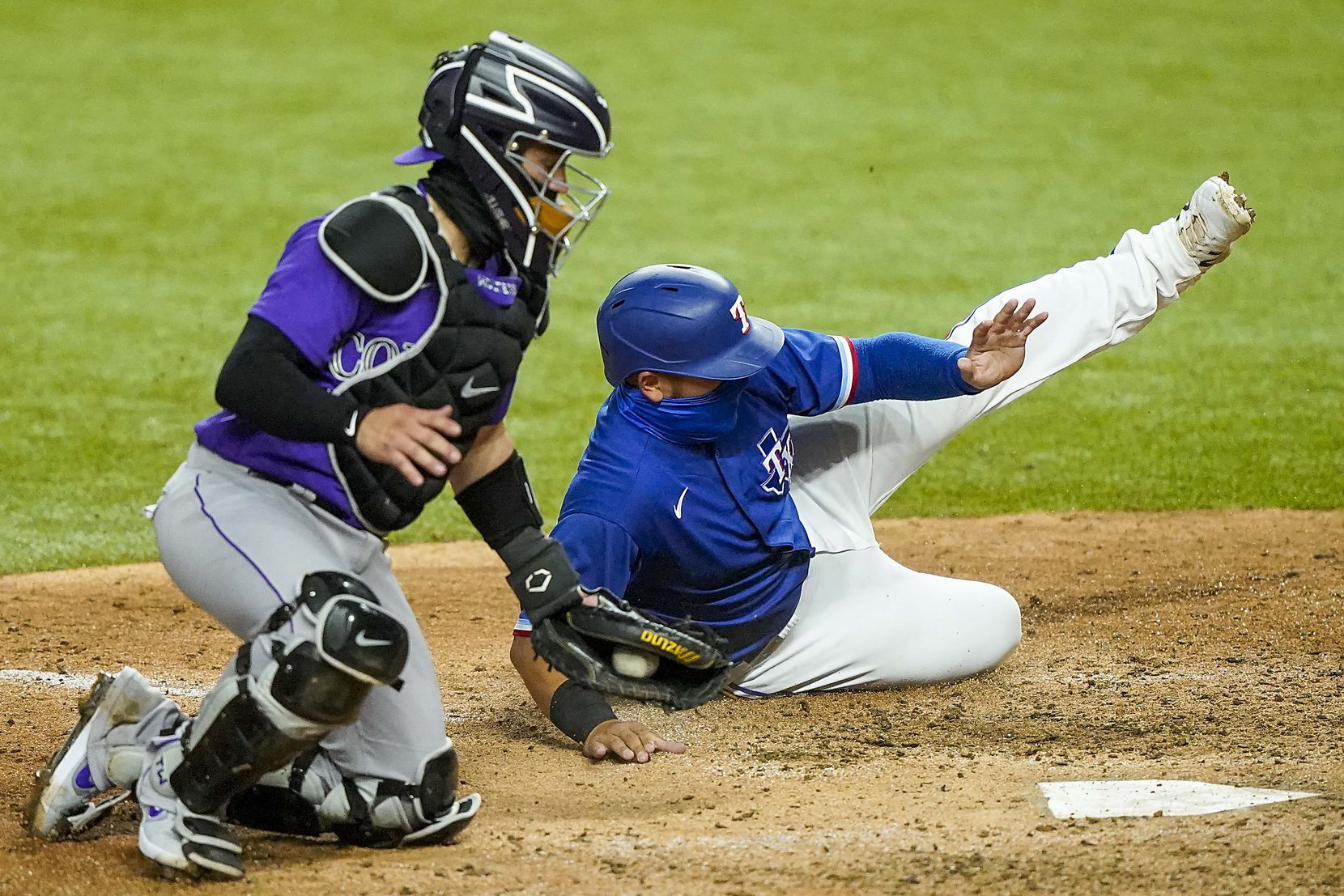 Texas Rangers catcher Jose Trevino is thrown out at home trying to score on a double by outfielder Nick Solak as Colorado Rockies catcher Tony Wolters makes the tag on a throw by center fielder David Dahl during the sixth inning of an exhibition game at Globe Life Field on Tuesday, July 21, 2020.