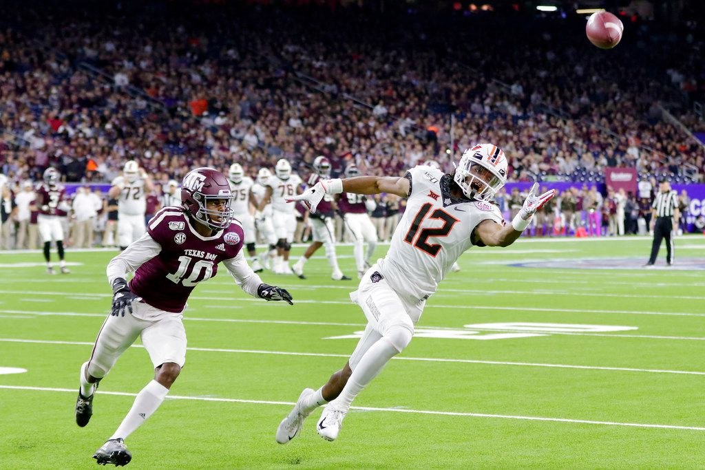 FILE - Oklahoma State wide receiver Jordan McCray (12) reaches for an overthrown pass in front of Texas A&M defensive back Myles Jones (10) during the first half of the Texas Bowl NCAA college football game Friday, Dec. 27, 2019, in Houston. (AP Photo/Michael Wyke)