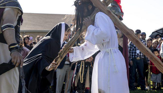 Gema Martínez (representando a María) se inclina ante Fernando León (Jesucristo) en el viacrucis viviente en la iglesia St. Philip The Apostle en Dallas. (Shaban Athuman/DMN)