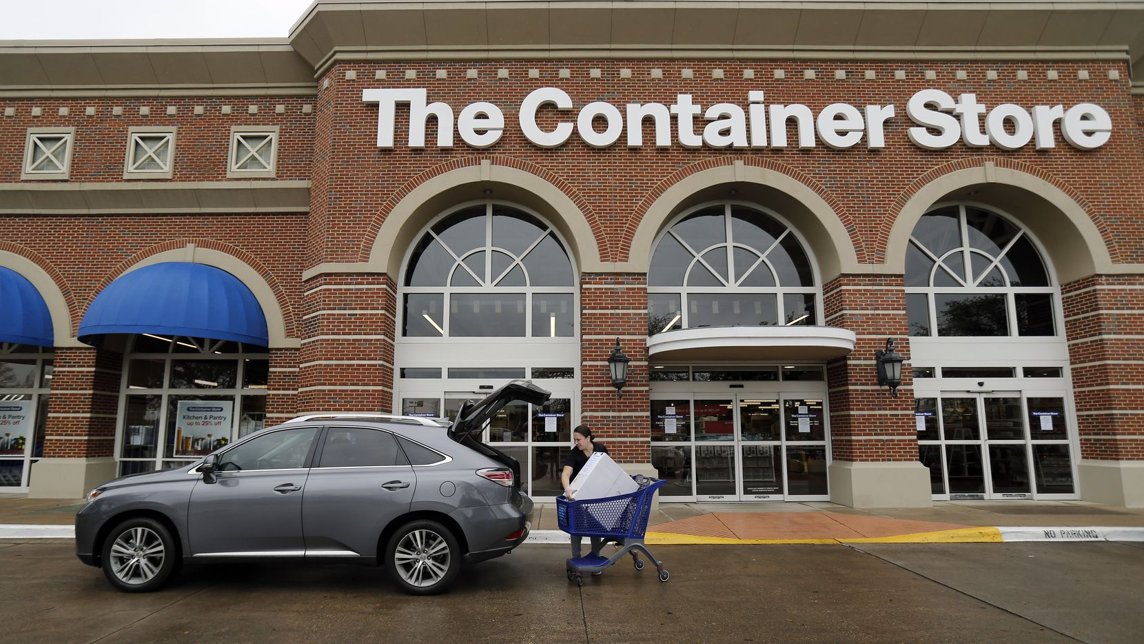 An employee at The Container Store loads an order for a customer waiting in the curbside pickup line at the store on Northwest Highway in Dallas.