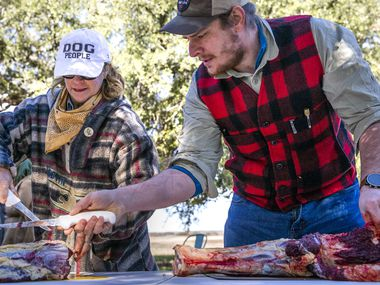 Jacob Arthur (right) from Austin, Texas, gives advice to Cindee Klement as they debone a cut of bison during a daylong bison field harvest event at Roam Ranch in Fredericksburg, Texas, on Sunday, Jan. 19, 2020.