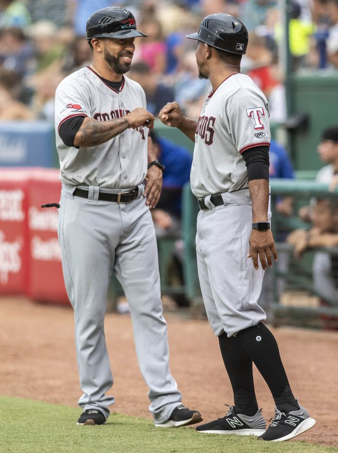 Hickory Crawdad's coach Hiram Bocachica and manager Joshua Johnson bump fists during the game with the Greensboro Grasshopper's at First National Bank Field on Friday, August 6, 2021 in Greensboro, N.C. (Woody Marshall/Special Contributor)