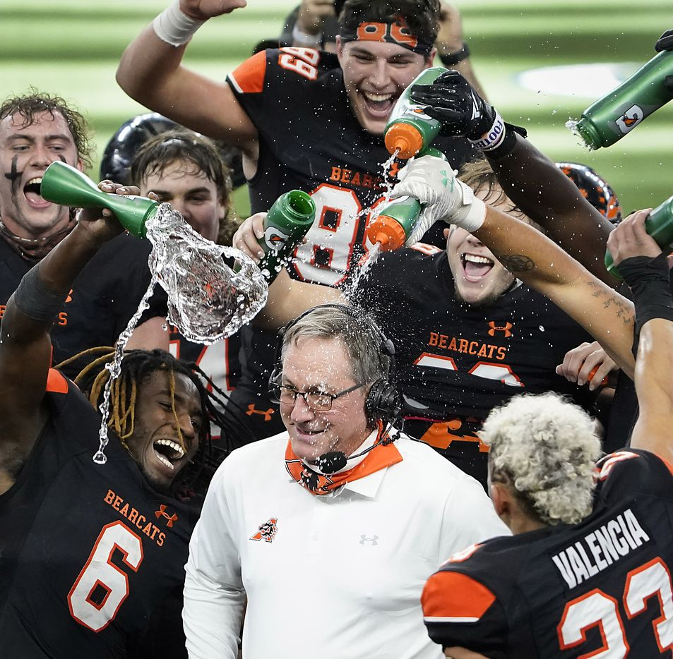 Aledo running back DeMarco Roberts (6), the offensive MVP of the game, leads the charge as head coach Tim Buchanan is doused by his players as the Bearcats celebrate after a 56-21 victory over Crosby to win the Class 5A Division II state football championship game at AT&T Stadium on Friday, Jan. 15, 2021, in Arlington. The victory gave Aledo the 10th state championship in school history. (Smiley N. Pool/The Dallas Morning News)