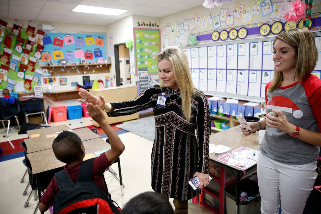 First grader Calen Simms, 6, gives principal Aimee Lewis a high five after correctly answering a math problem at McKenzie Elementary School in Mesquite, Texas on December 5, 2017. Lewis has been working in the Mesquite district for the past 28 years. First grade teacher at right is Logan Cornelison.