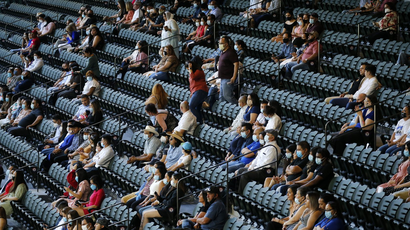 Guests wearing masks were socially distanced in their ticketed seats for Irving's Jack E. Singley Academy commencement at Globe Life Field in Arlington on Friday, May 29 2020. The graduation ceremony is also the first public event held at the newly constructed ballpark. Because of the COVID-19 pandemic, previous events including the start of the Texas Rangers season have been put on hold. Singley Academy is the first of 49 graduations from 18 Independent School Districts in North Texas that will take place at Globe Life Field through the end of June. (Tom Fox/The Dallas Morning News)