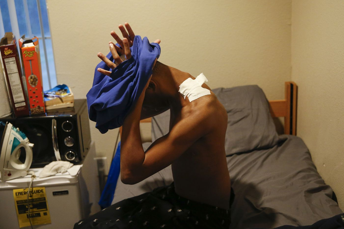 Jaylon Miller stretches a shirt over his head as a bandage covers a gunshot wound on his shoulder at the University of North Texas at Dallas on Thursday, Jan. 30, 2020 in Dallas.