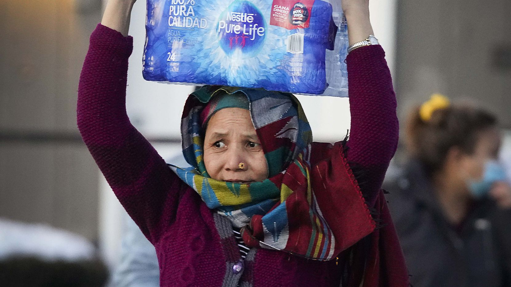 A woman carries two cases of drinking water distributed at the Literacy Achieves nonprofit in Vickery Meadows to nearby residents living without water after a winter storm brought snow and continued freezing temperatures to North Texas on Thursday, Feb. 18, 2021, in Dallas.