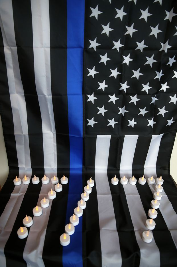 """Candles in the shape of the date """"7/7"""" and a """"Thin Blue Line"""" flag honor the fallen officers of the July 7, 2016 ambush attack, shown at Dallas Police Headquarters in Dallas, on Friday, July 7, 2017. The Thin Blue Line is a symbol used by law enforcement to commemorate fallen officers."""