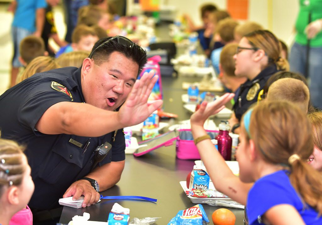 Hickory Creek police officer Mike Miller high fives a Corinth Elementary student during their Red, White and Back the Blue Day at the school Friday September 11, 2015, in Corinth, Tx. Photo by Al Key/DRC