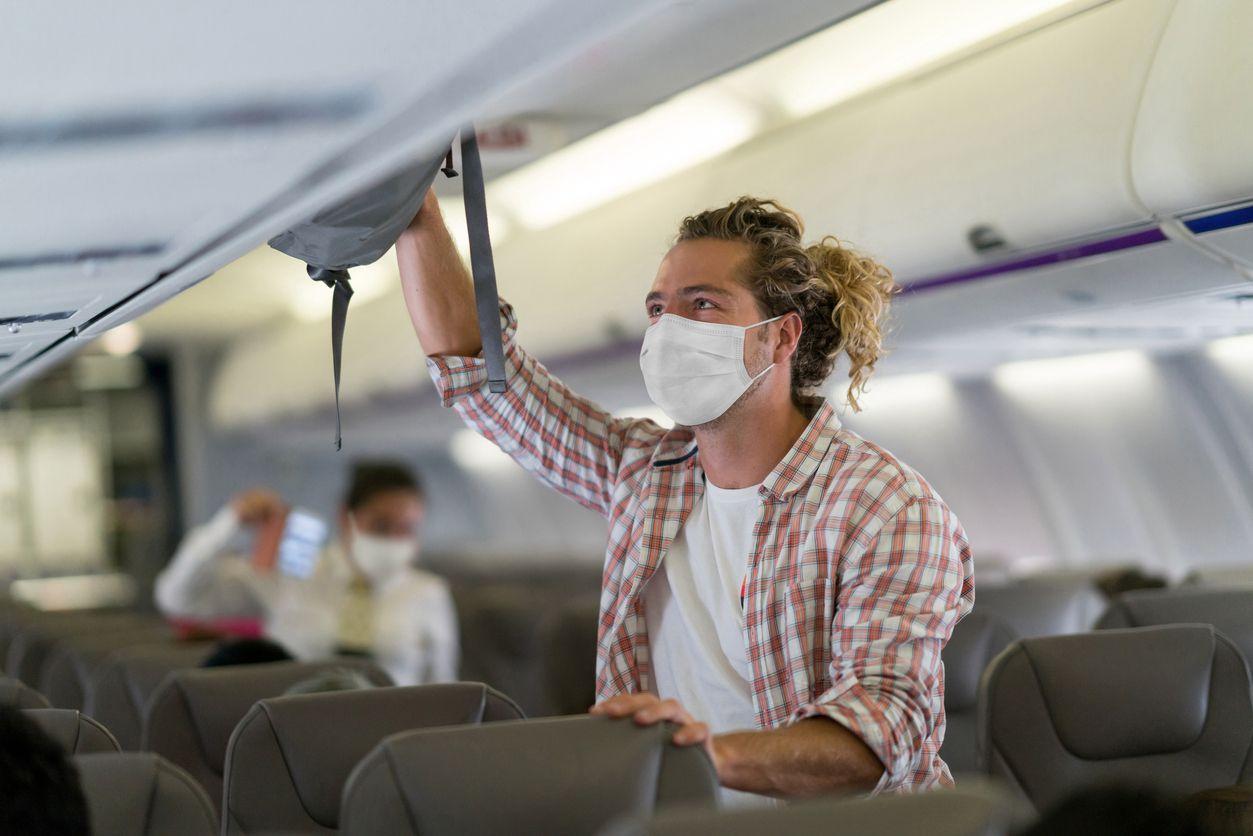 Un pasajero con mascarillas ubica su equipaje en el compartimento de la cabina de un avión, antes de tomar un vuelo.