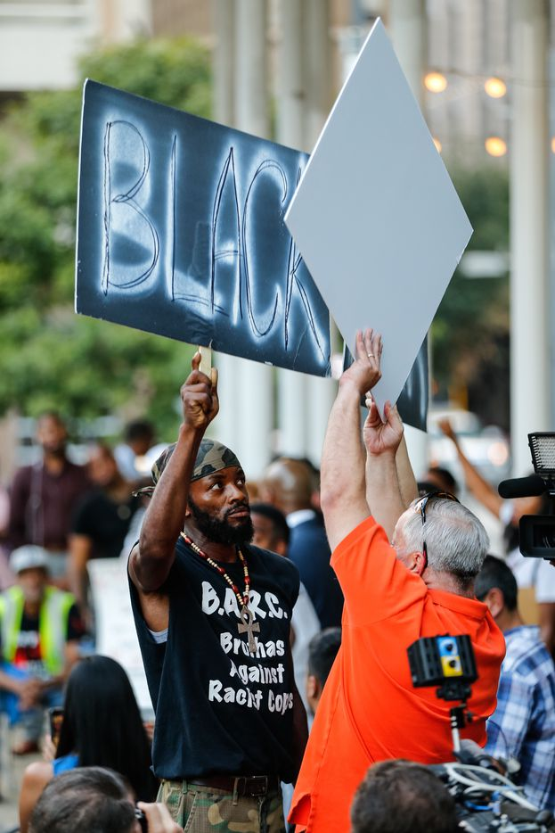 A protestor who goes by the name Solahkiyah (left) tries to block the message of police supporter Douglas Peyton, of Little Elm, TX, (in orange) as the Next Generation Action Network was holding a Enough is Enough protest standing in solidarity with the families and all of those who want justice for all, Thursday, September 22, 2016 at Main St Garden in downtown Dallas. (Tom Fox/The Dallas Morning News)