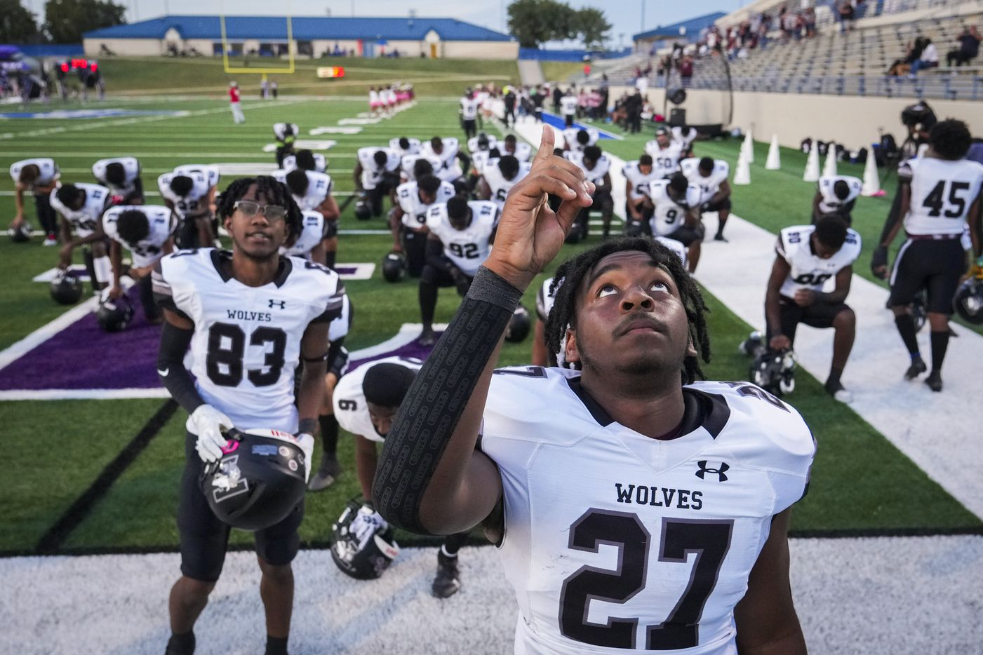 Mansfield Timberview's Deshaun Pratt (27) points skyward after kneeling in prayer with his teammates before facing Waco University in a high school football game at Waco ISD Stadium on Friday, Oct. 8, 2021, in Waco, Texas. A shooting following a classroom fight on Wednesday injured four people at Timberview High School.