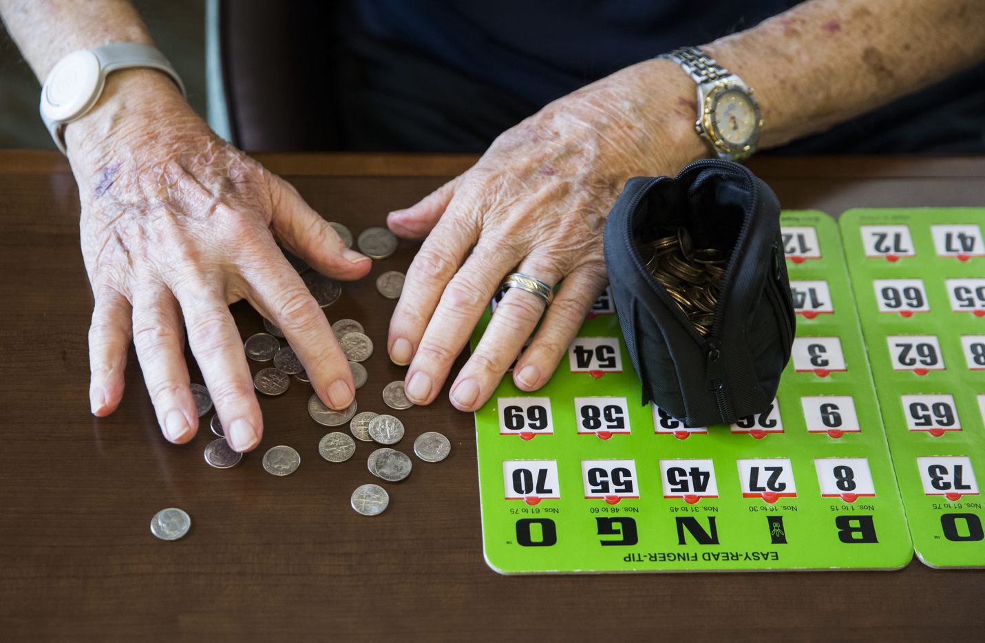 Bob Stiegler sorts dimes to play bingo.  It costs a dime to play each card.