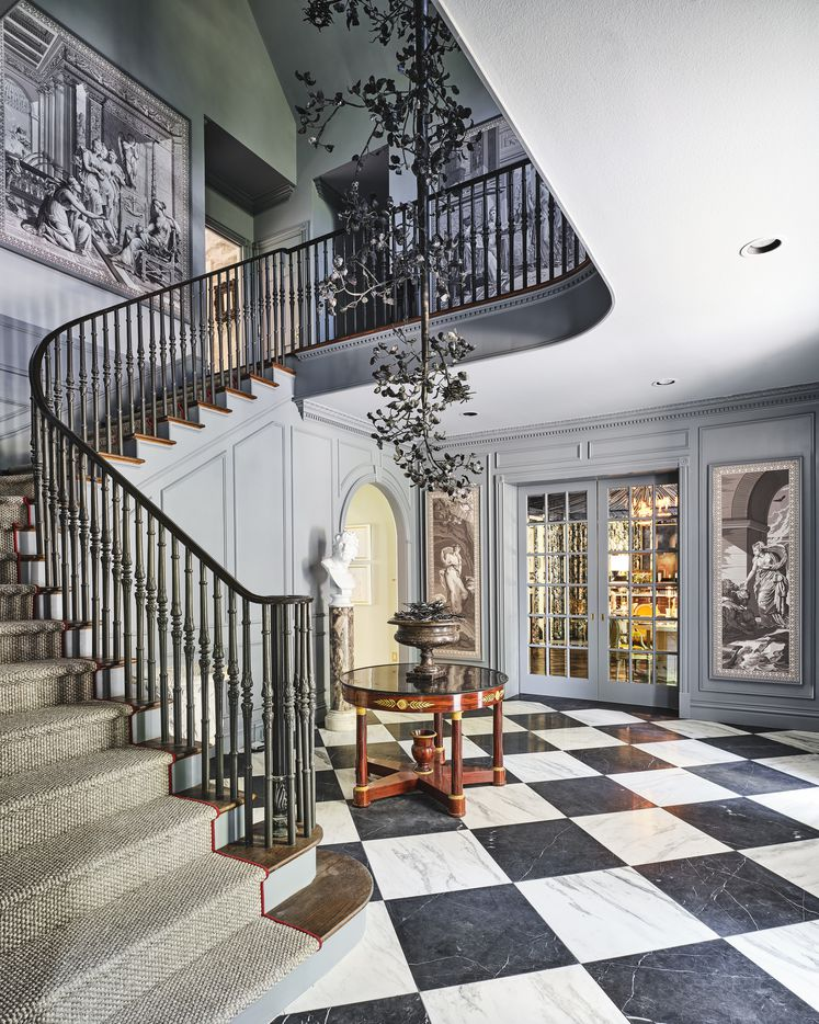 Bobbitt & Company Interior Design crafted the entry hall and foyer for the 2021 Kips Bay Decorator Show House Dallas. The design has a winding staircase, elements of classical art and architecture and a large sculpture by artist Larry Whiteley that is suspended from the ceiling and is visible from the first and second levels.
