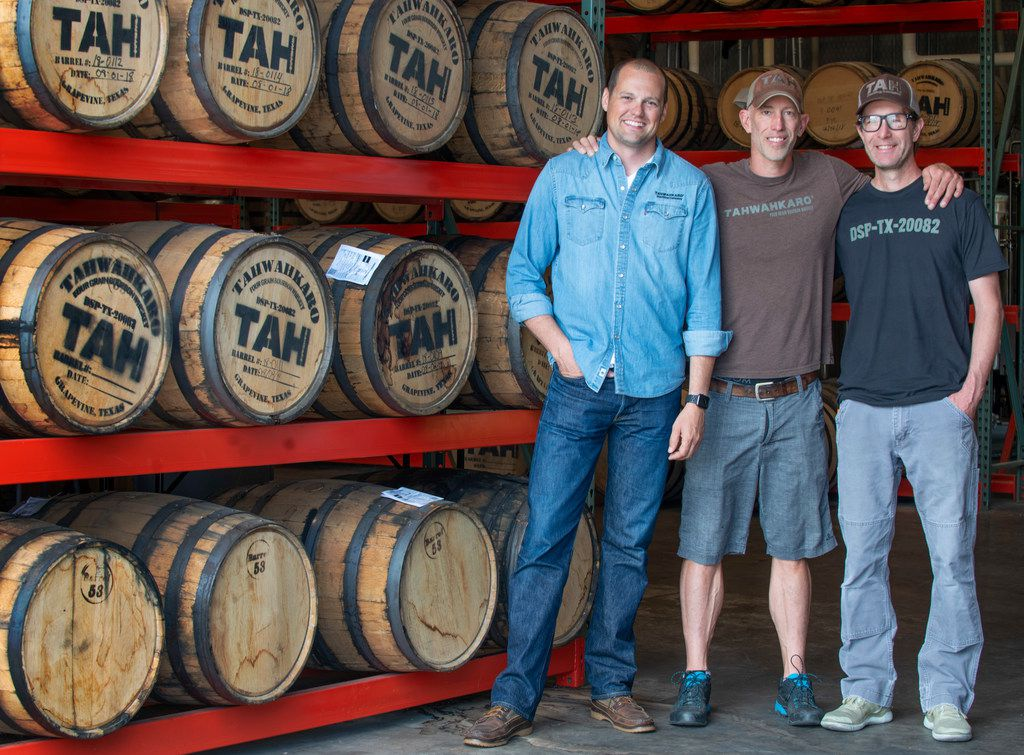 Chris Vivion, left, Jason Jackson and brother Justin Jackson, owners of Tahwahkaro craft distillery with barrels of their four-grain bourbon whiskey in Grapevine, Texas on June 7, 2019.