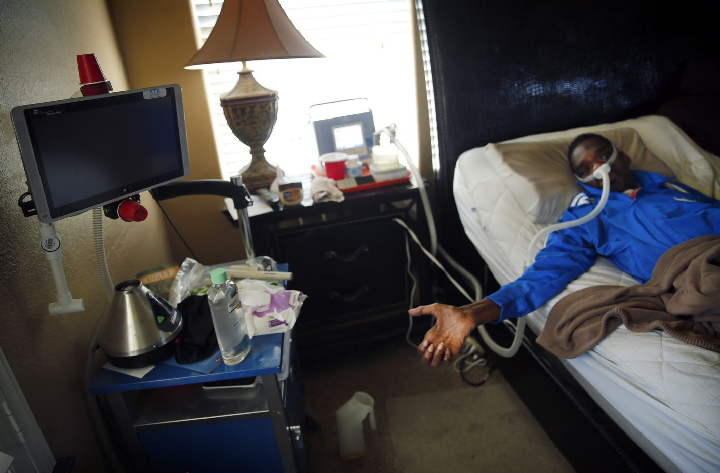 Rickey Dixon uses a thumbs up signal when something excites him or answers yes to a question. Here he is on an aspirator as he lays in bed at their Red Oak, Texas home, Friday, April 7, 2017.  (Tom Fox/The Dallas Morning News)