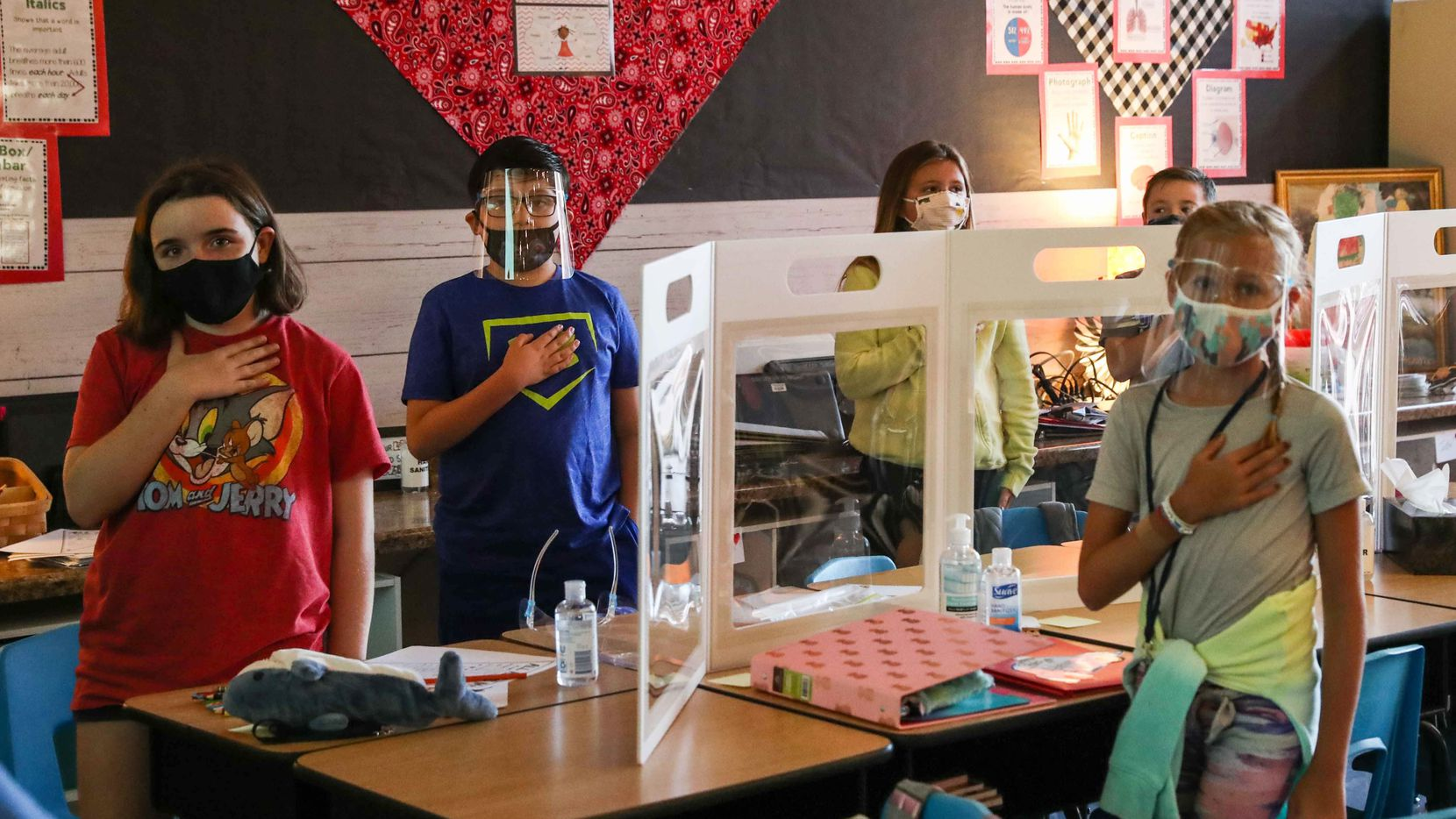 4th grade students wearing masks and face covers, take the pledge of allegiance at Jacobs Well Elementary school on its first day of class in Wimberley on Wednesday, August 19, 2020.