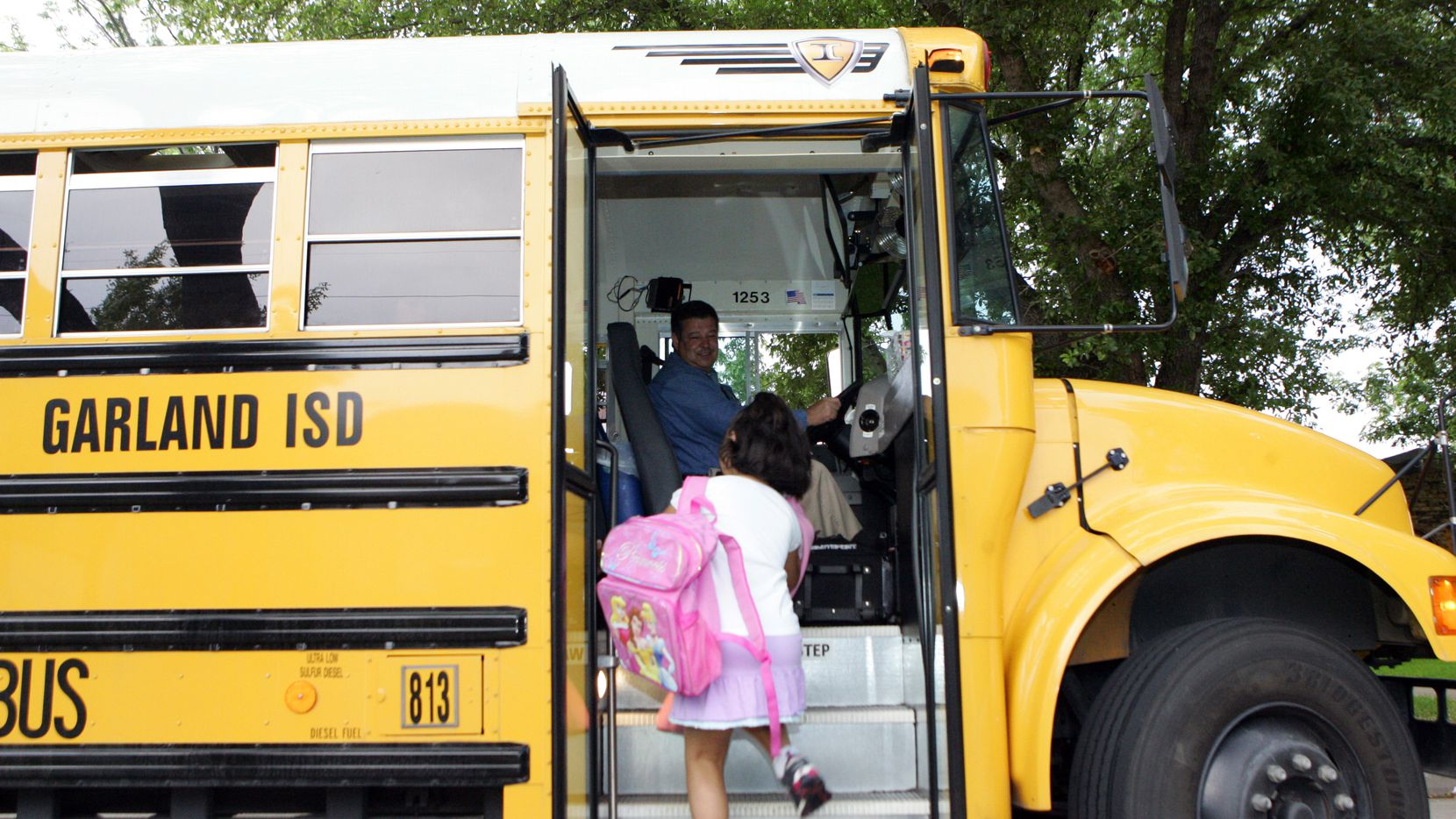 Garland Independent School District bus driver Parker Abell (left) greets Rosa Medrano as she boards the bus for Hillside Elementary and Watson Technology Center in Garland, Texas, Tuesday, May 9, 2006.