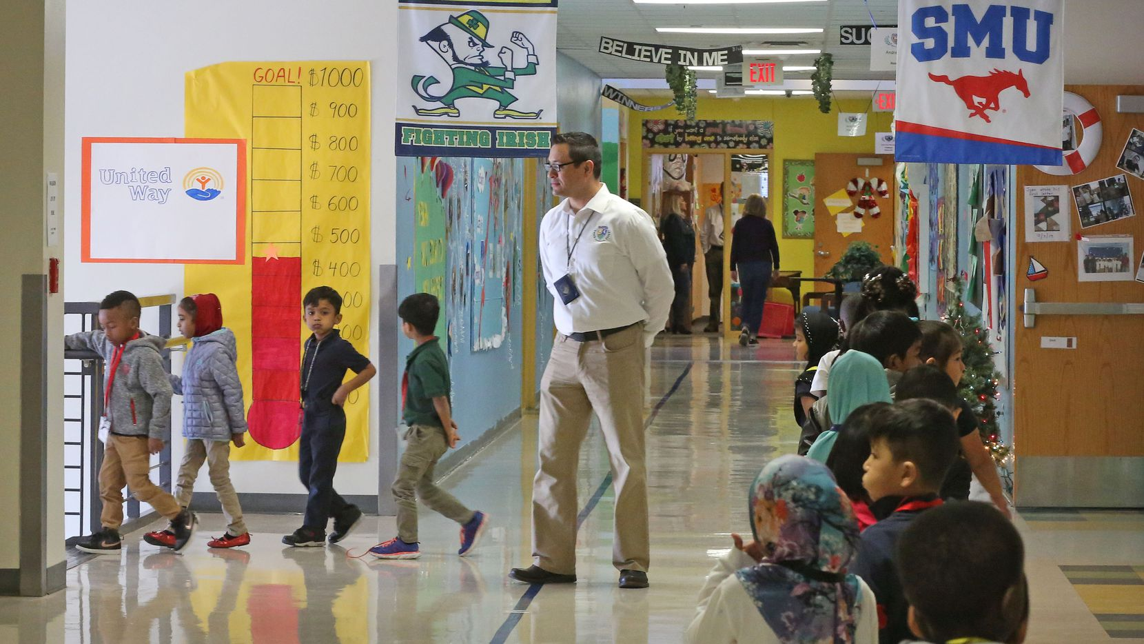 Teacher Assistant Adrian Rivera watches as students make their way through the hallways at Dallas ISD's McShan Elementary in Vickery Meadow.