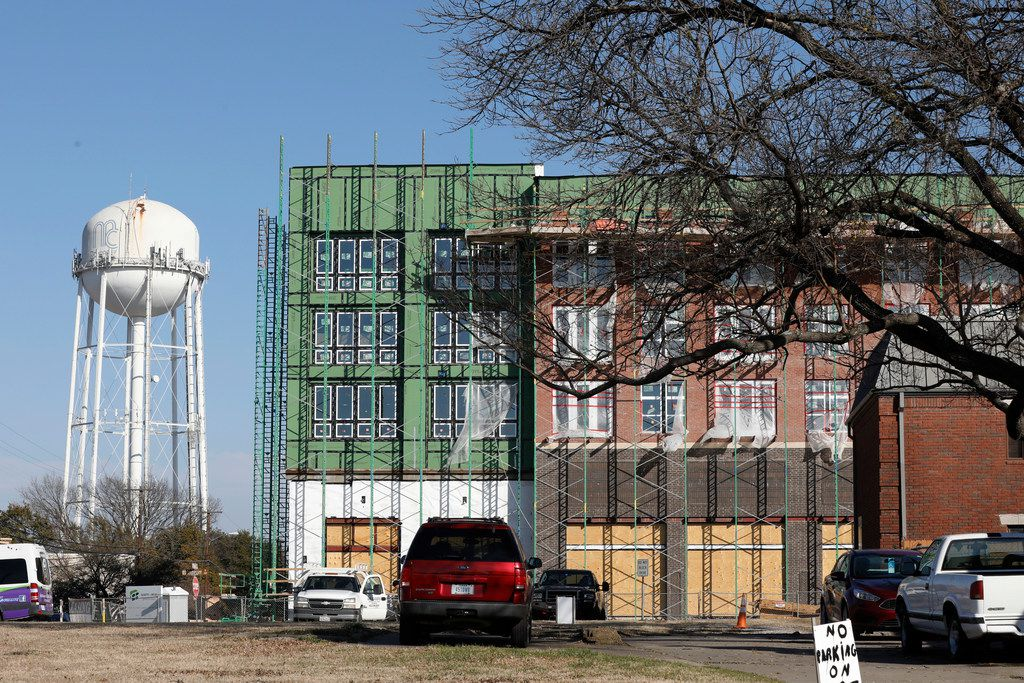 An old McKinney water tower emerges behind new construction in downtown McKinney. Residents will receive water-rate adjustments and other waivers related to the winter storm, thanks to a resolution passed by city council.