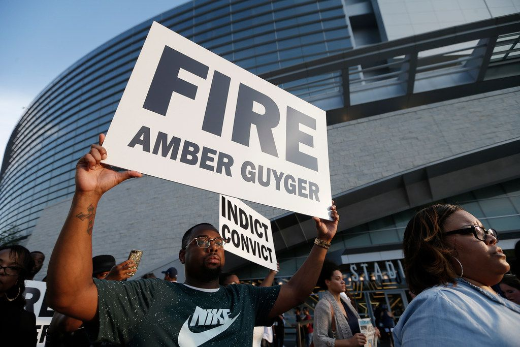 Demonstrators at AT&T Stadium Sunday night demanded Dallas Police fire Amber Guyger, who shot and killed Bortham Jean in his apartment two weeks ago.
