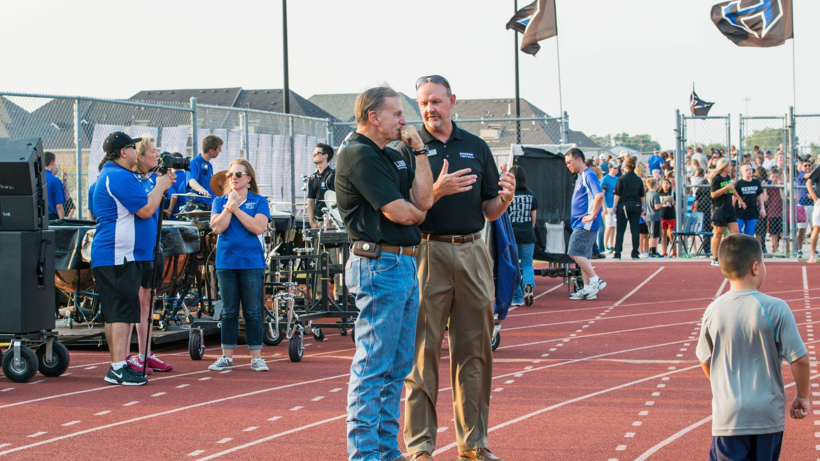Lewisville ISD athletic director Tim Ford (left) talks to former Hebron principal Scot Finch during a football game in 2015. (Photo courtesy of Lewisville ISD)