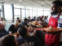 Dallas Cowboys running back Ezekiel Elliott (right) helps serve an early Thanksgiving lunch to clients at The Salvation Army Carr P. Collins Social Service Center in Dallas on Tuesday, November 19, 2019.