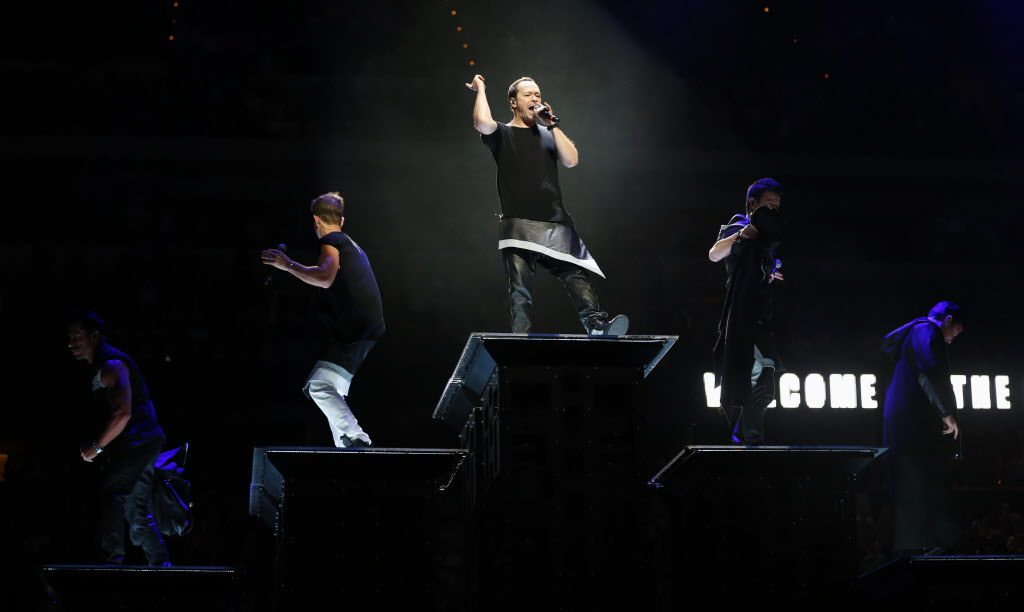 New Kids on the Block's Donnie Wahlberg (center) and band members sing during a performance at American Airlines Center in Dallas, on Thursday, May 14, 2015.
