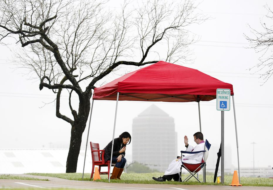 Under a light mist, the Rev. Michael Picard (right), a Regnum Christi priest, prayed for Anabel Cardova of Coppell as he listened to her confessions at The Highlands School in Irving. Priests took confessions from parishioners under tents as they drove up in their cars Sunday, March 22, 2020. With public spaces shut down amid the coronavirus pandemic, churches are getting creative about providing sacramental relief to their members.(Tom Fox/The Dallas Morning News)