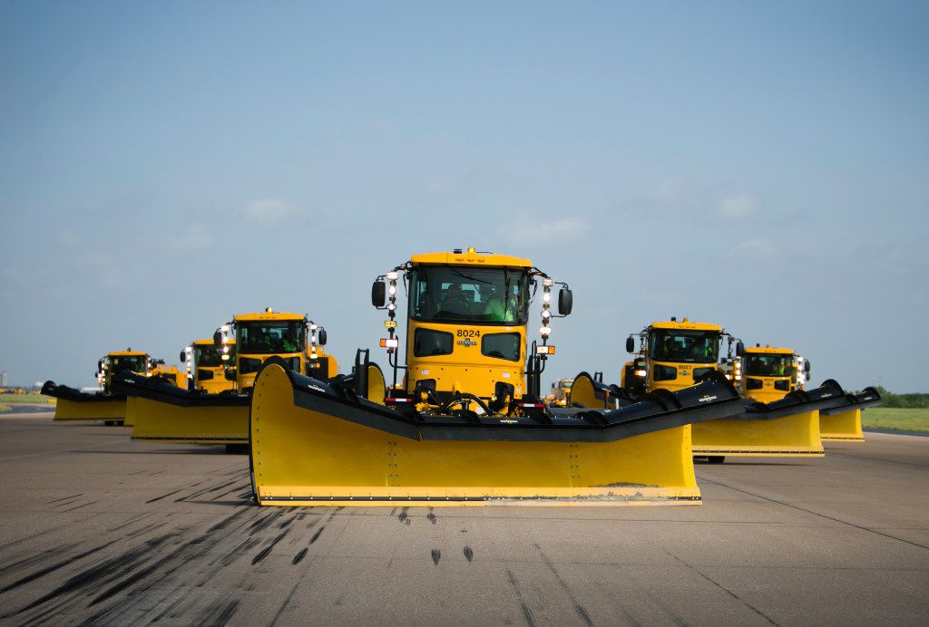 Snowplows make their way down a runway during a training session at DFW International Airport.