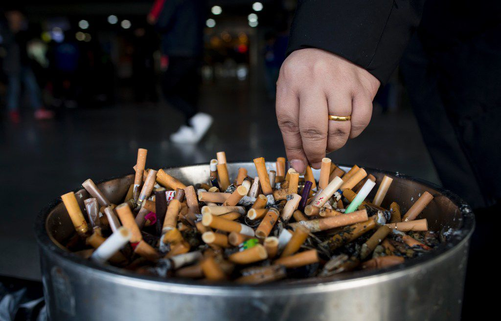 In this photo taken on February 28, 2017, a man grinds out his cigarette in an ashtray at a railway station in Shanghai. AFP PHOTO / Johannes EISELEJOHANNES EISELE/AFP/Getty Images