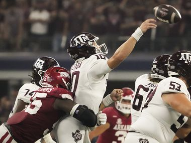 Texas A&M quarterback Zach Calzada (10) is hit by Arkansas defensive lineman Tre Williams (55) as he gets off a pas during the second half of an NCAA football game at AT&T Stadium on Saturday, Sept. 25, 2021, in Arlington. Arkansas won the game 20-10.