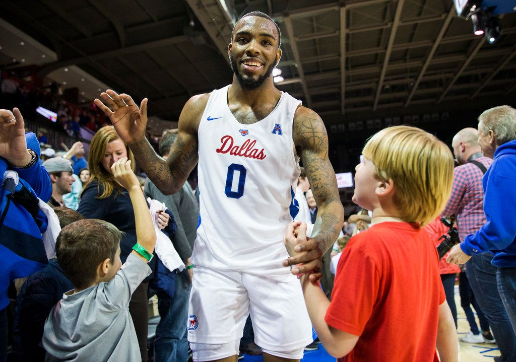 Southern Methodist Mustangs guard Tyson Jolly (0) high-fives fans after a 73-72 win in overtime of a basketball game between SMU and University of Houston on Saturday, February 15, 2020 at Moody Coliseum in Dallas. (Ashley Landis/The Dallas Morning News)