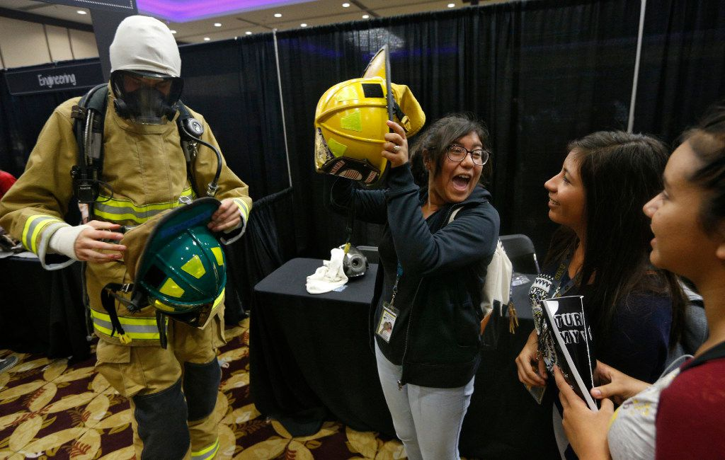 Xitlali Parra (center) from John Adams Middle School is excited to put on a fire helmet next to Tyler Uptain (left) from Grand Prairie High School Fire Academy as a part of the My Future My Way exhibit spotlighting the school district's Career and Technical Education programs at Asia Times Square in Grand Prairie.