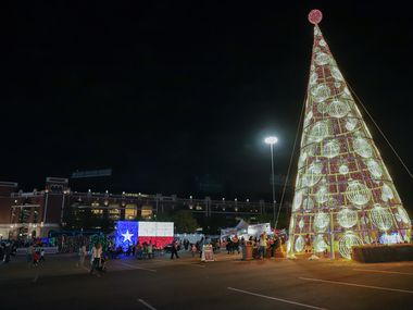 Guests make their way around a 65-foot-tall Christmas tree at Luminova Holidays at Globe Life Field in Arlington in November. During the COVID-19 pandemic, many holiday events are taking a different form in Arlington and elsewhere.