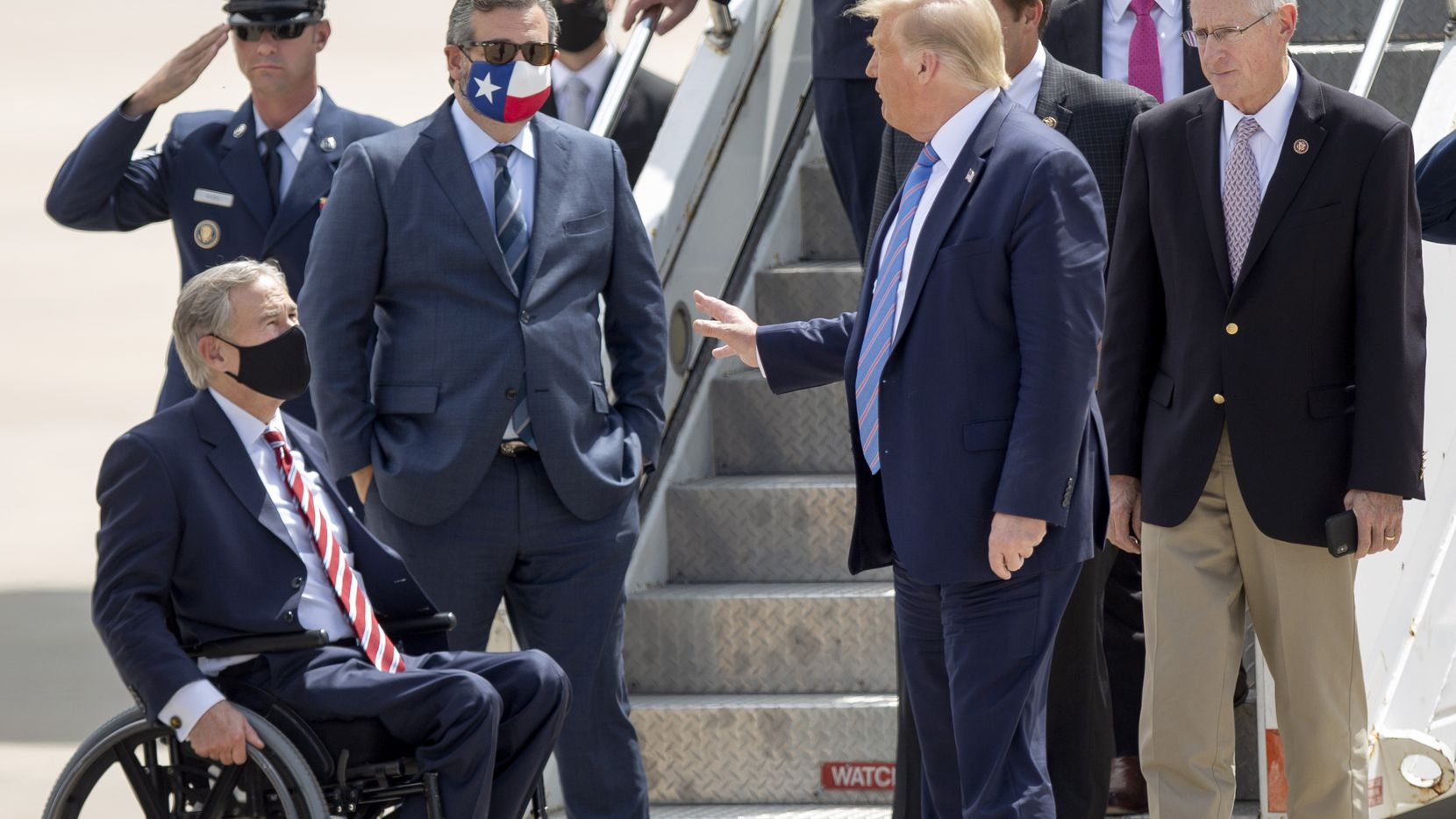 President Donald Trump chats with Texas Gov. Greg Abbott and Sen. Ted Cruz, with Rep. Mike Conaway, right, after arriving in Midland on Wednesday, July 29, 2020.