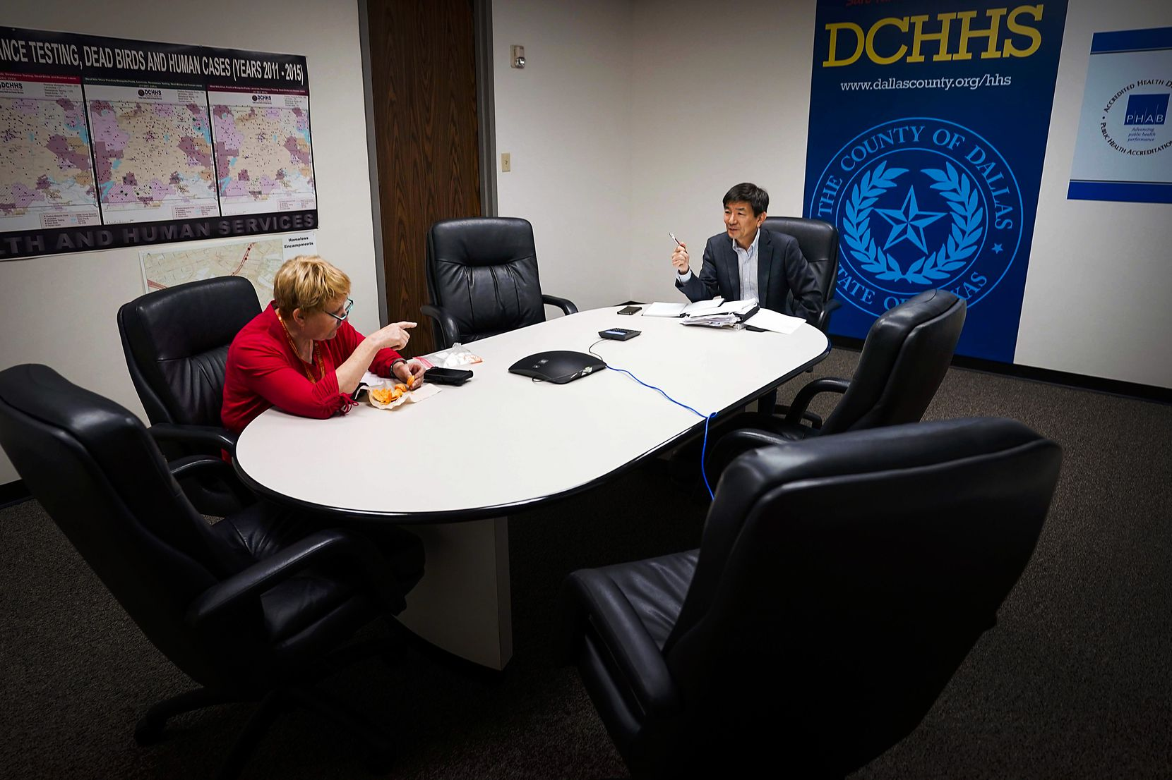 Dr. Philip Huang, Dallas County Health and Human Services director, and Dr. Joann Schulte, deputy health authority and medical director, kept social distance as they met with other staff by conference call at DCHHS offices on April 8, 2020.