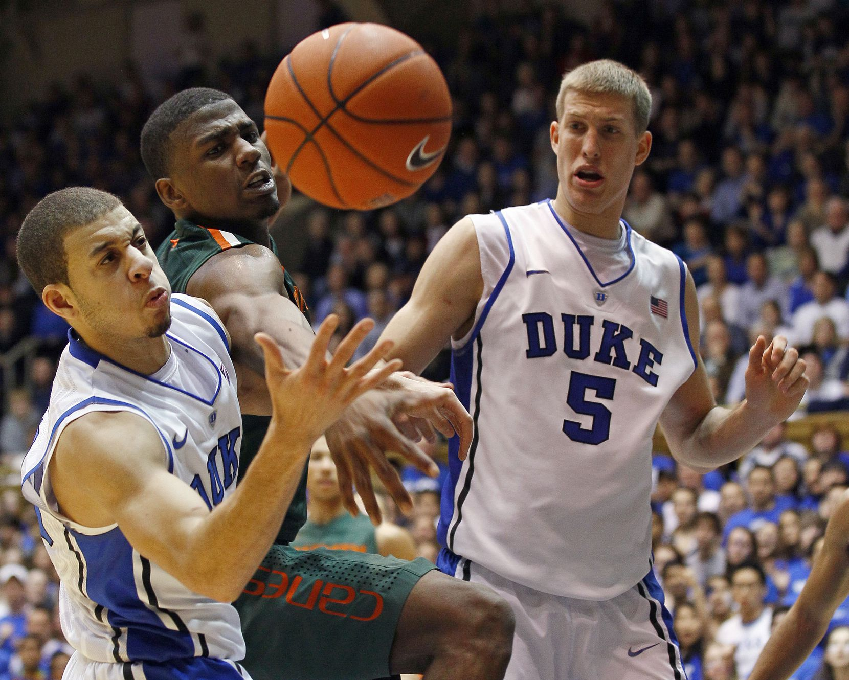 Duke's Seth Curry, left, and Mason Plumlee (5) struggle for a rebound against Miami's DeQuan Jones during the second half  of an NCAA college basketball game in Durham, N.C., Sunday, Feb. 5, 2012. Miami won 78-74 in overtime. (AP Photo/Gerry Broome)