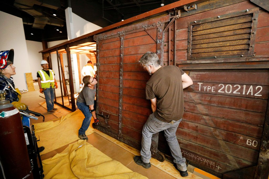 Carpenter Jeff Green (right) and lead carpenter Dennis Manske erect a door on the rail car that's on display at the new Dallas Holocaust and Human Rights Museum. The car was brought to Dallas from Belgium and housed in the Jewish Community Center until now. The car was restored and moved by pieces into the new museum.