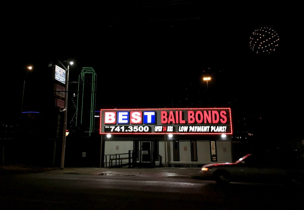 Lights from a bail bond business glow along Riverfront Boulevard in Dallas.