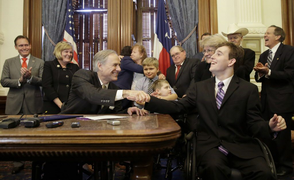 Texas Gov. Greg Abbott, front left, shakes hands with Zachariah Moccia, right, who has dravet syndrome, after he signed SB 339, a bill allowing the medical use of low-THC cannabis, into law at the Texas Capitol June 1, 2015 in Austin.