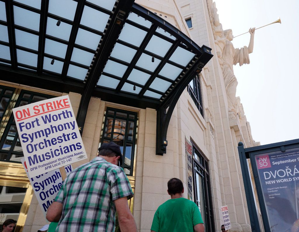 Striking Fort Worth Symphony musicians picket under the Bass Hall angels.